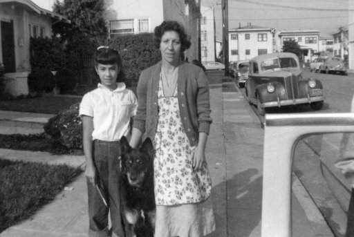 Old photo of a woman, girl and a dog on the street in 1950s
