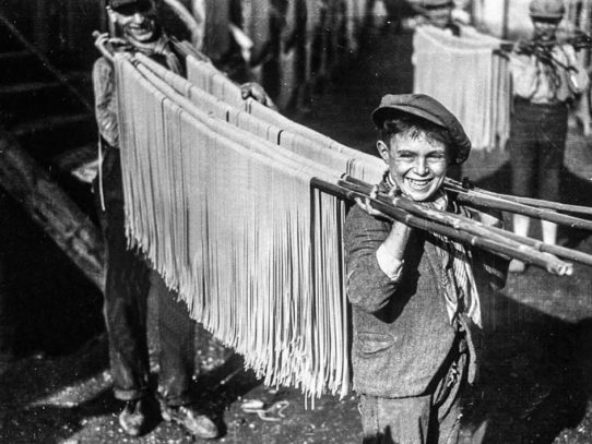 Boys carrying strings of pasta, Naples, Italy, 1929