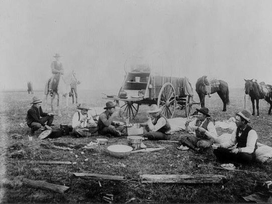 Cowboys having breakfast next to a chuck wagon, 1905