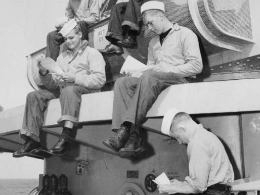 Sailors reading mail onboard the USS Helena from California to Japan, 1951
