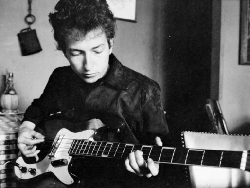 Bob Dylan plays a bass guitar in a restaurant, 1964