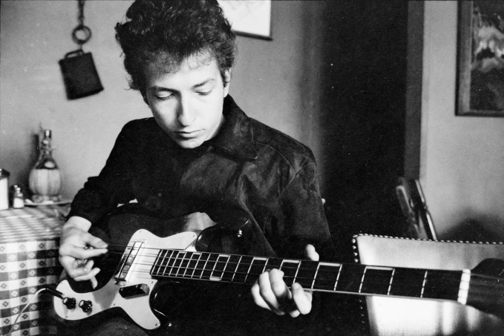 Bob Dylan plays a bass guitar in a restaurant, 1964