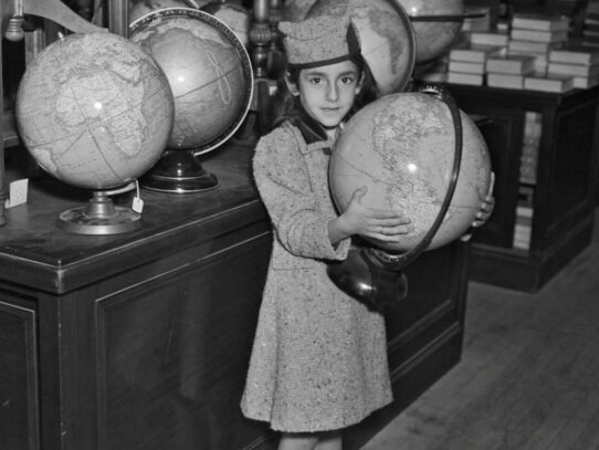 Girl holding a globe in a Los Angeles shop, 1937