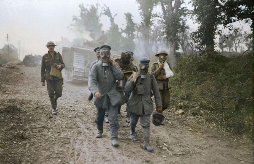 Battle of Amiens. Tanks advancing. Prisoners bring in wounded wearing gas masks. August, 1918
