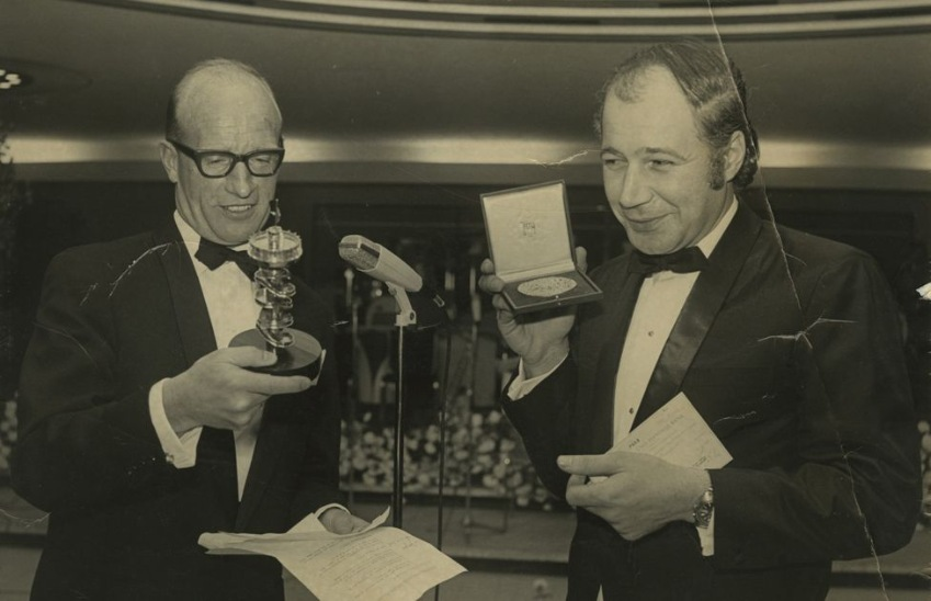Eddie Adams (right) holds up his Pulitzer Prize