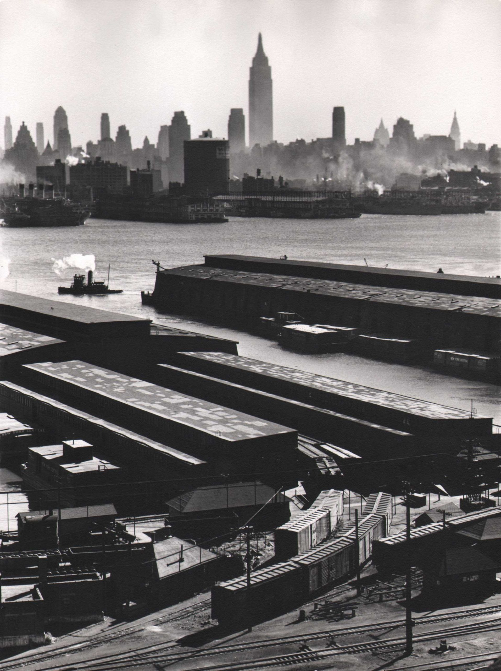 Esther Bubley, Weehawken, New Jersey. View looking east from 50th Street and East Boulevard showing New York Central piers, Hudson River and Midtown Manhattan skyline, 1946.