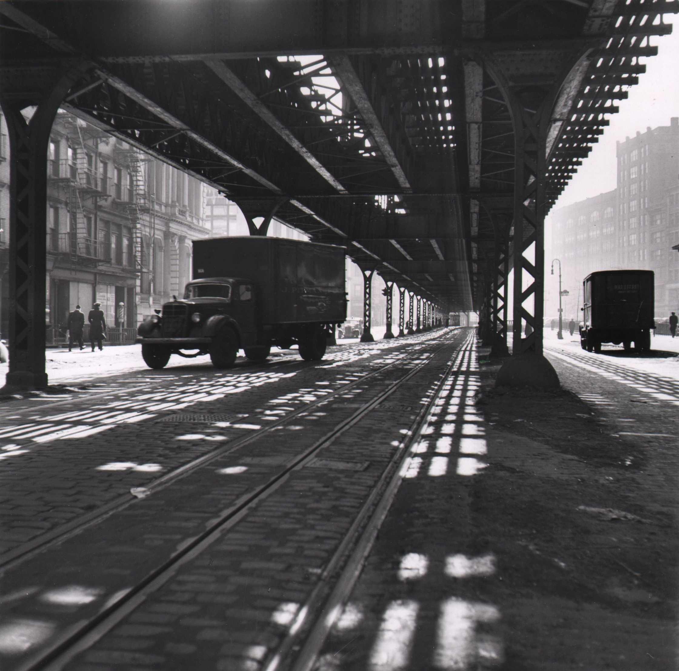 Louise Rosskam, New York City- Trucking. Trucks under the Third Avenue elevated platform, 1945