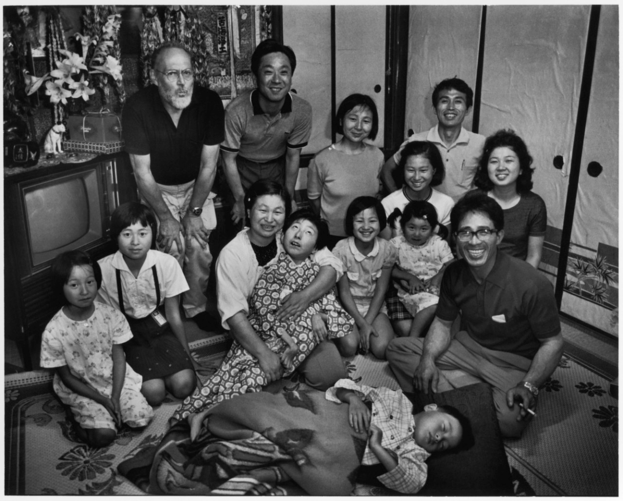 Tomoko with her family, supporters, Gene, and Asahi Camera editor, taken at Tomoko's home in Minamata on her sixteenth birthday. Photo by Aileen M. Smith. June 13, 1972.