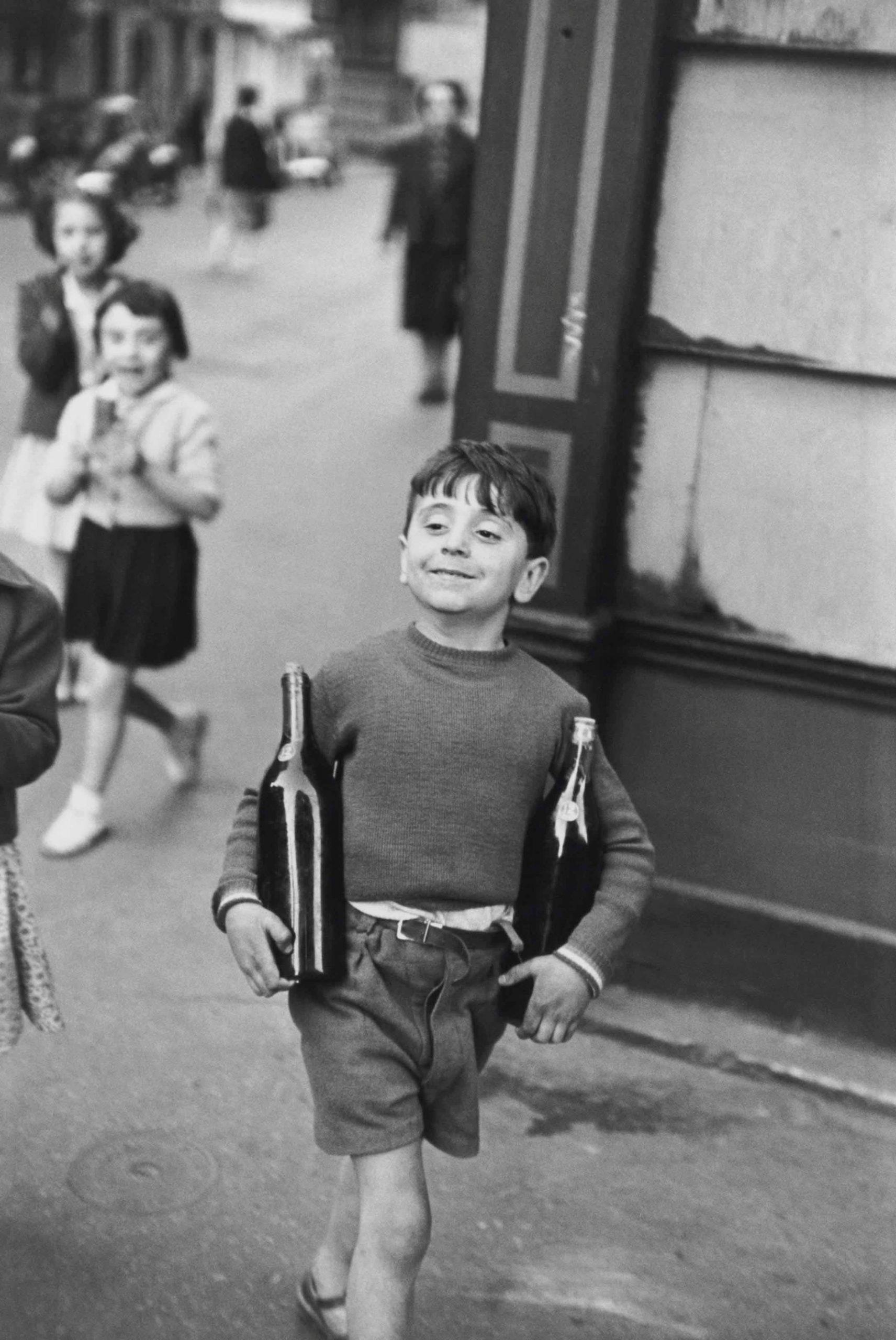 A boy carrying wine bottles, Henri Cartier-Bresson photos