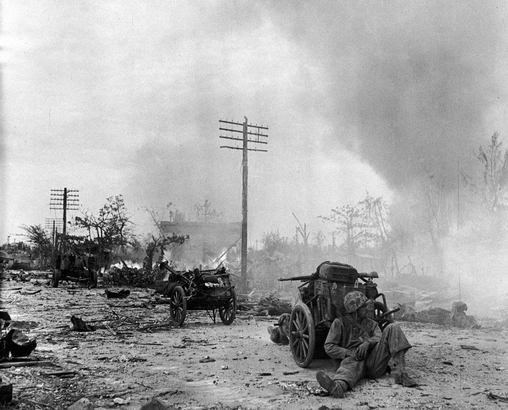 A U.S. Marine rested behind a cart on a rubble-strewn street during the battle to take Saipan from occupying Japanese forces.