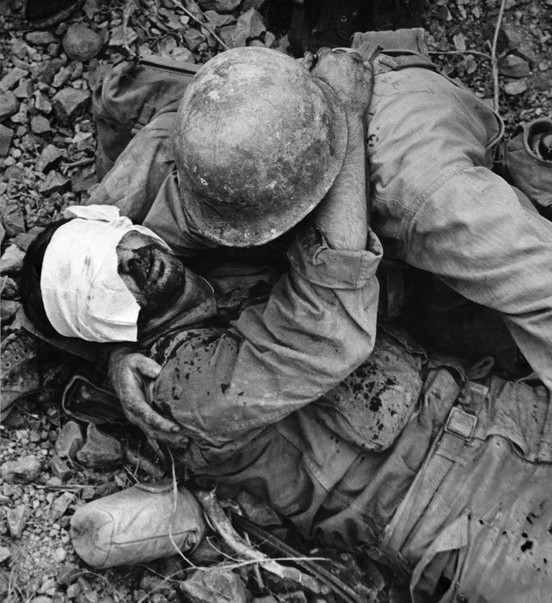 A US soldier helps a wounded soldier from his unit.