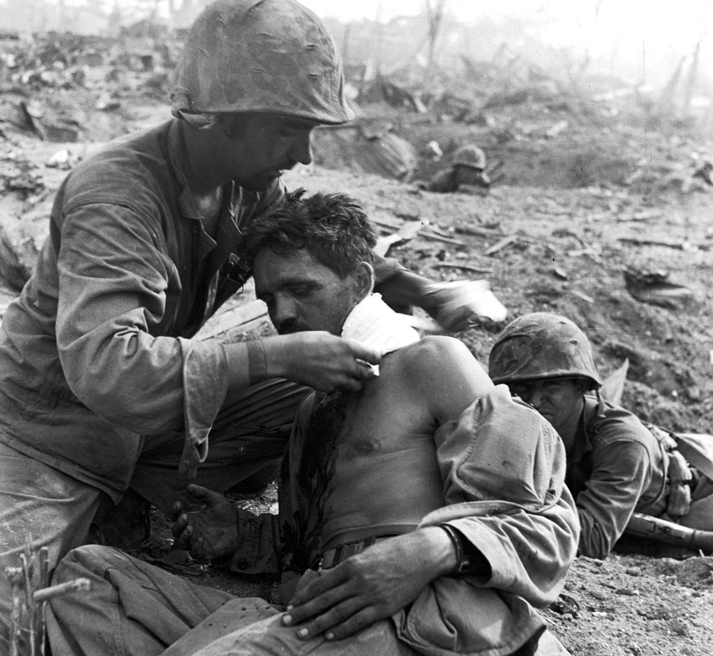 A medic tended to a wounded soldier during a fierce battle to take Saipan from occupying Japanese forces.