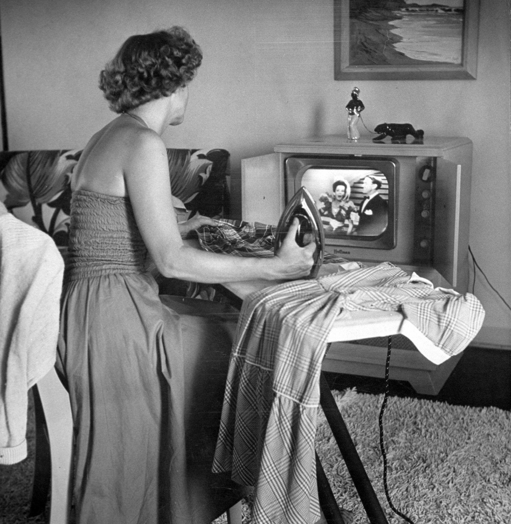 A woman irons while watching T.V., 1952.