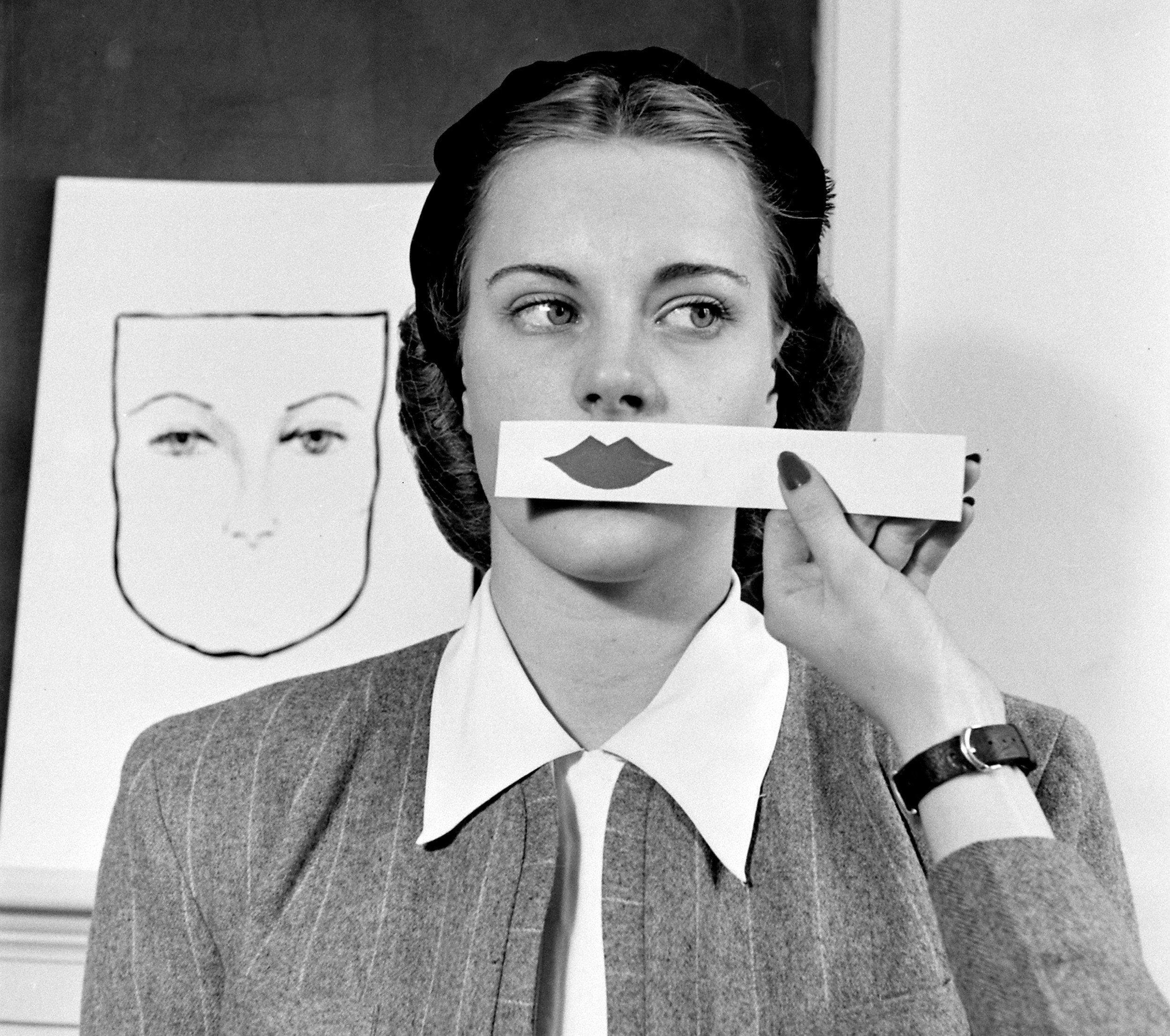 A woman samples different shades of lipstick on a strip of paper at Stephens College in Columbia, Missouri, 1945.