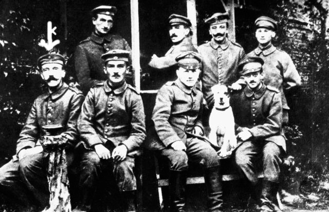 A young Hitler (farthest left at bottom row) posing with other German soldiers and their dog
