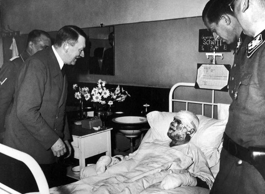Adolf Hitler visits wounded in the July 20, 1944, assassination attempts. The injured man in the bed is Walter Scherff, Hitler's military historian