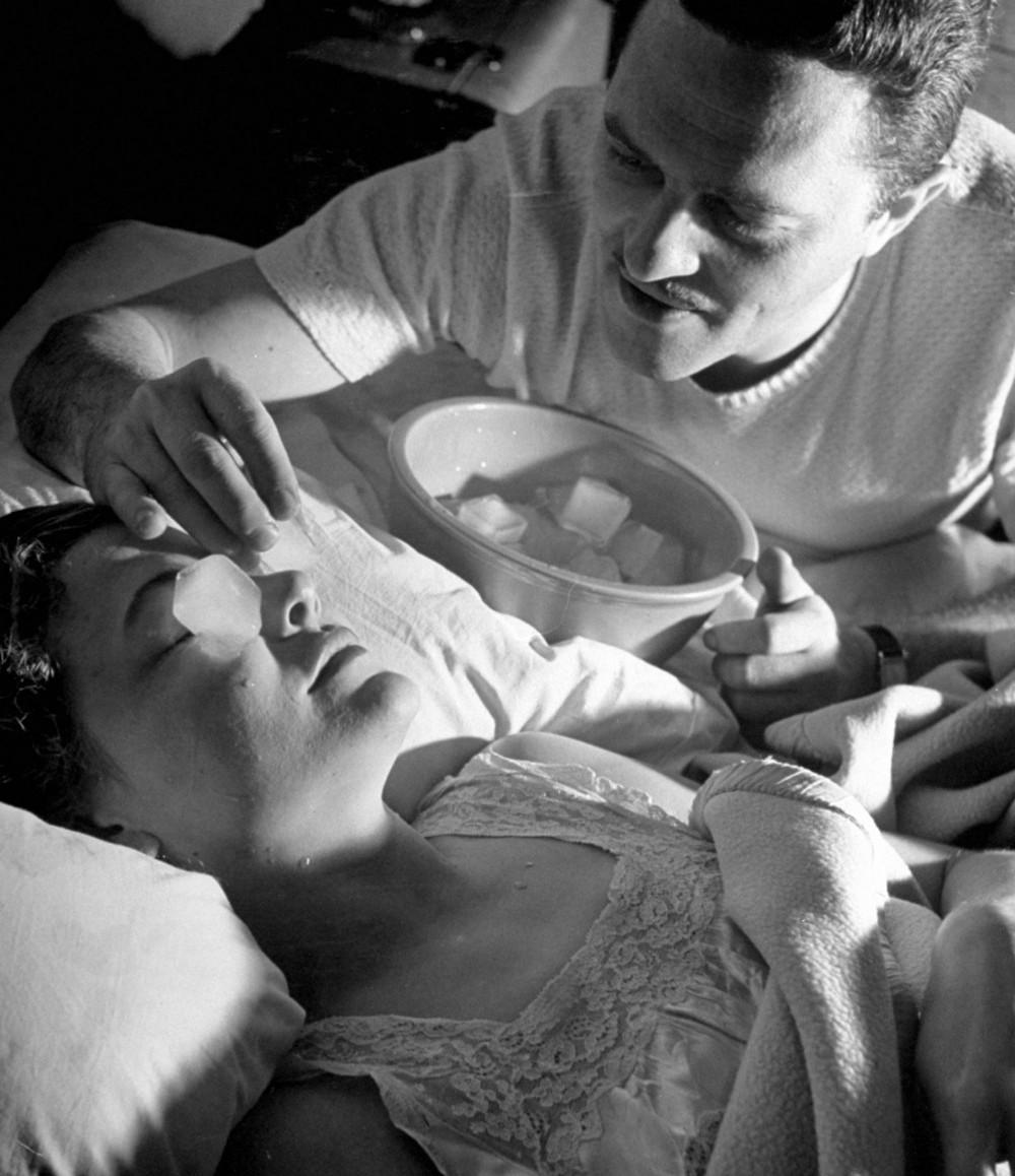 Brazilian musician Bernardo Segall giving wife Valerie Bettis an ice cube treatment, 1948