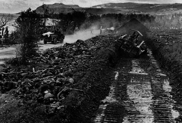 Bulldozer scooping out the grave for 2000 Japanese soldiers