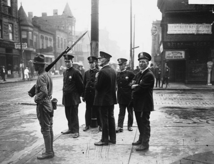 Chicago police officers and a soldier of the Illinois National Guard on a South Side street corner during the 1919 riots.