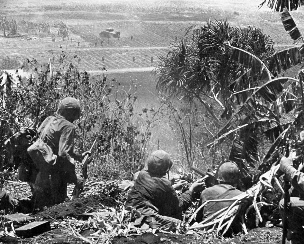 Marines followed tanks against the last Japanese defenders with machine gunners providing cover. Three men alongside the photographer were hit just before he took the picture.