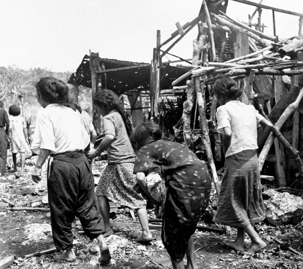 Native civilians fled ruins of a village during the fighting between Japanese and American forces for control of Saipan.