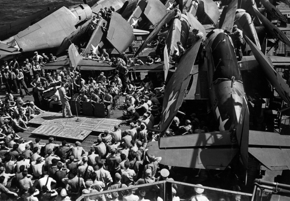The crew of the USS Bunker Hill aircraft carrier being briefed before the attack