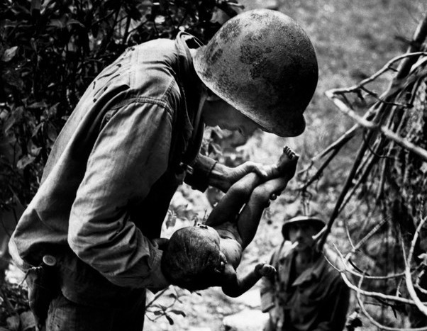 US marine holding a wounded Japanese kid during WW2