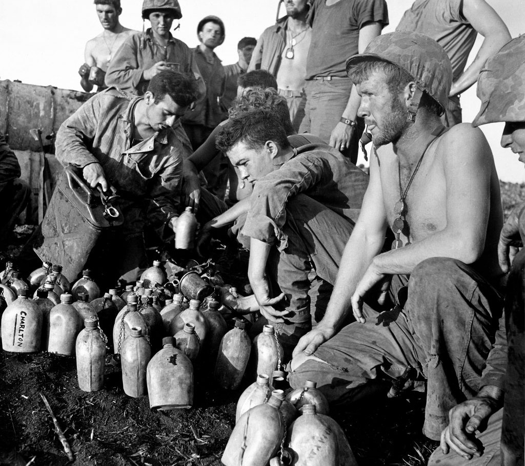 Weary Marines filled canteens with water while the fighting raged on during the battle to wrest control of Saipan.