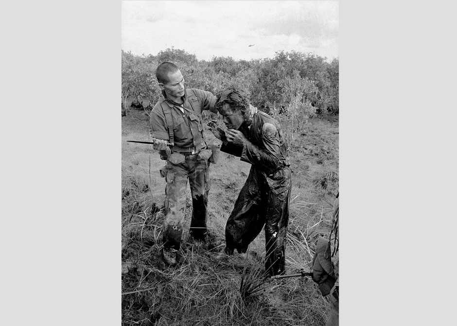 A South Vietnamese soldier hits a farmer with a dagger for giving false information to government forces about the movement of Viet Cong guerrillas in a village west of Saigon, Vietnam on January 9, 1964.