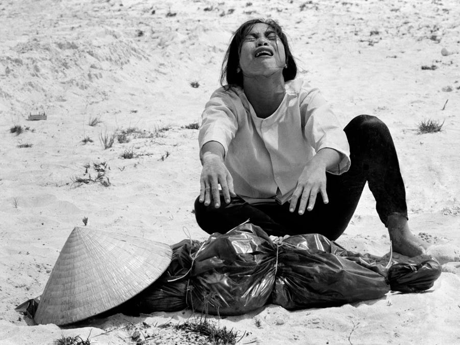 Horst Faas photo of South Vietnamese woman mourns over the body of her husband, found with 47 others in a mass grave near Hue, Vietnam.