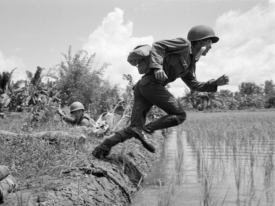 A Vietnamese medic jumps from a secure position behind a rice paddy dike, crossing a swampy paddy under fire from Viet Cong guerrillas, August 8, 1966. He was coming to the aid of wounded regional forces.
