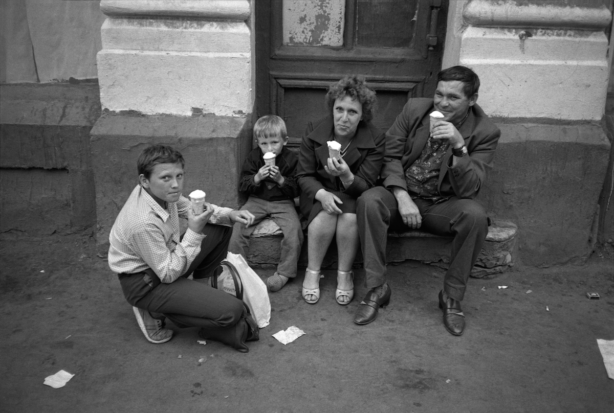 A soviet family is eating an ice-cream just on the pavement. There were not enough cafes and restaurants in the late soviet Moscow.