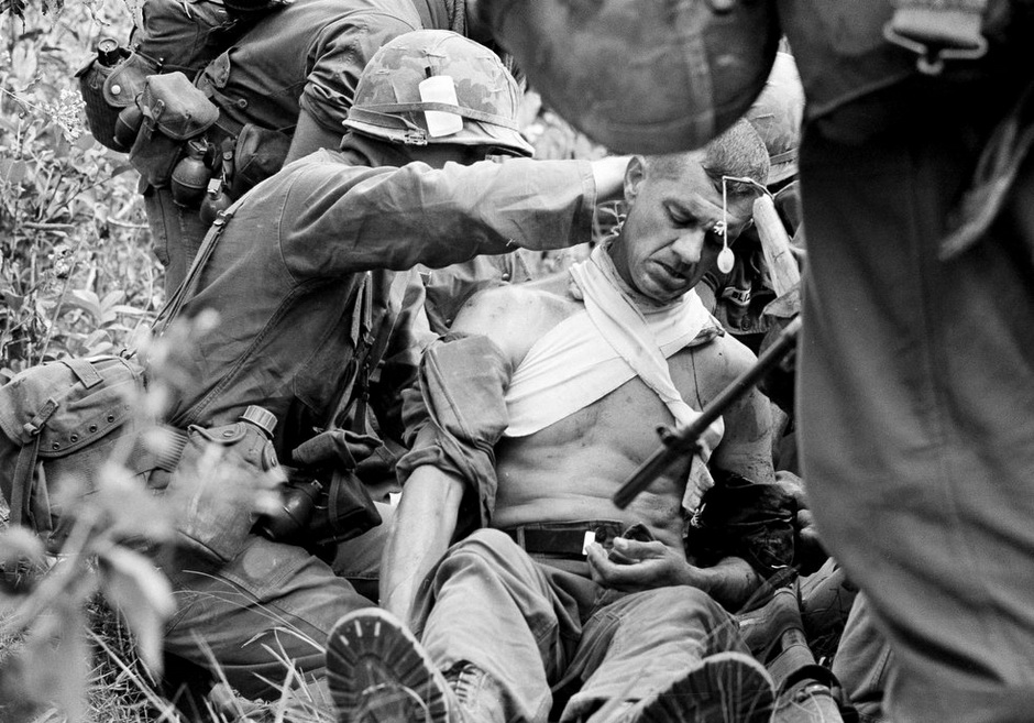 Horst Faas photo of American Lieutenant Colonel George Easter is carried on a stretcher after being wounded by a Viet Cong sniper in Chung Lap, South Vietnam, January 16, 1966.