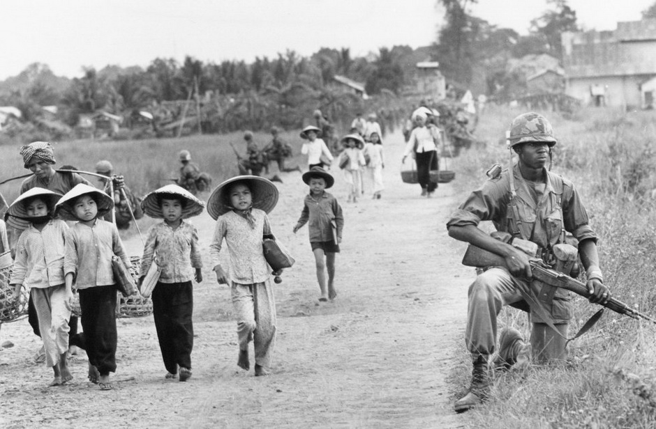 Horst Faas photo of American soldiers guard Route 7 as Vietnamese women and children return home to Xuan Dien village from Ben Khat, Vietnam, December 1965.