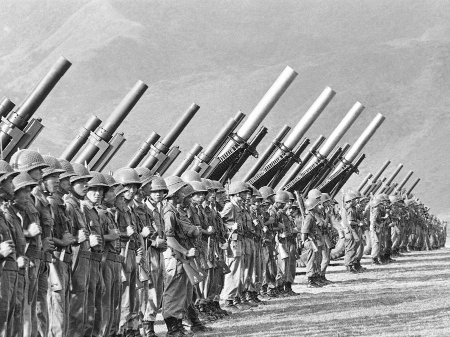 Artillery troops of the new South Vietnamese 25th division line up for a parade in front of 105 and 155 Howitzers in the coastal town of Quang Nai, South Vietnam, a Viet Cong stronghold, on August 15, 1962.