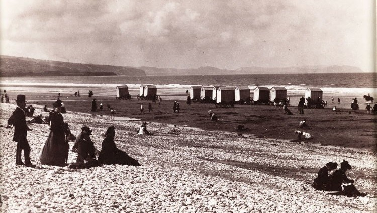 Daytrippers and rows of bathing machines at Pensarn Beach in North Whales, c. 1880