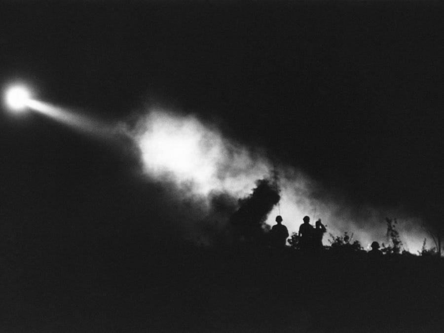Landing light from medical evacuation helicopter cuts through smoke of battle for Bu Dop, South Vietnam, silhouetting U.S. troops moving the most seriously wounded to the landing Zone on November 30, 1967.