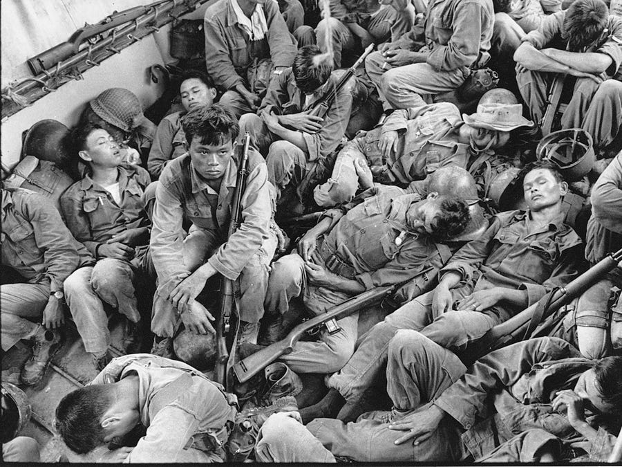 South Vietnamese government troops from the 2nd Battalion of the 36th Infantry sleep in a U.S. Navy troop carrier on their way back to the Provincial capital of Ca Mau, Vietnam.