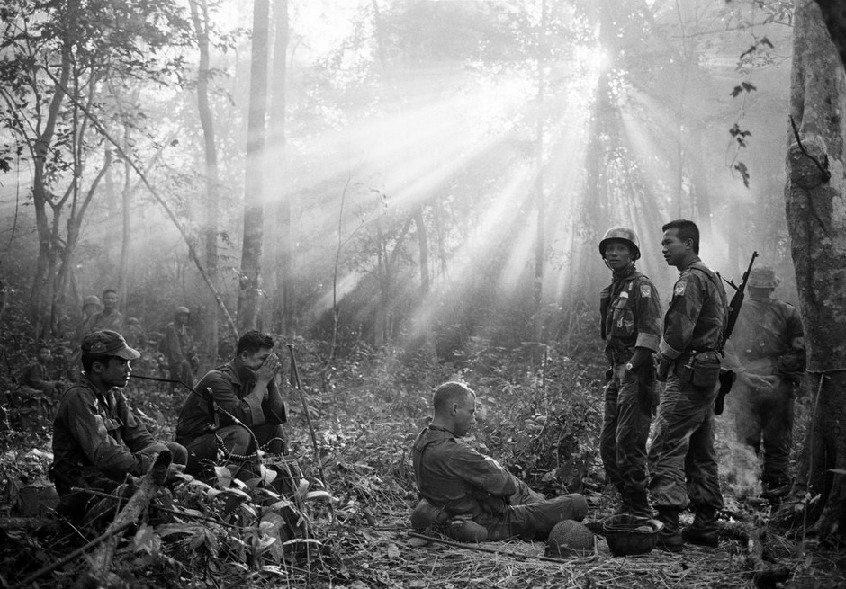 South Vietnamese troops, joined by US advisers, rest after a cold, wet and tense night of waiting in the dense jungle around the town of Binh Gia, 60 km from Saigon, Vietnam, in January 1965.