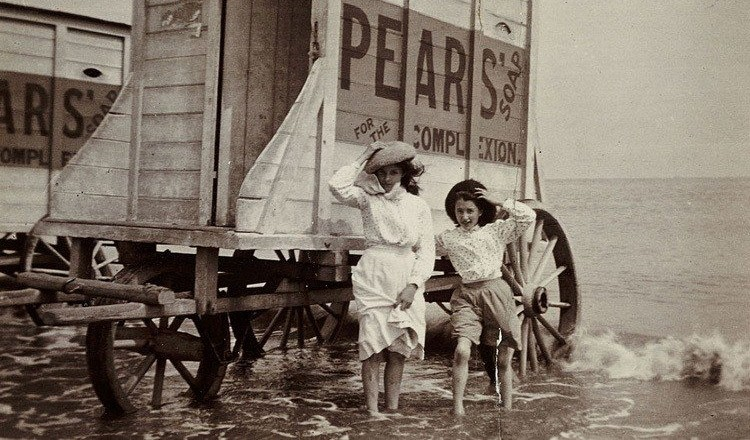 Two ladies wade beside a bathing machine adorned with advertisement for Pears' Soap.