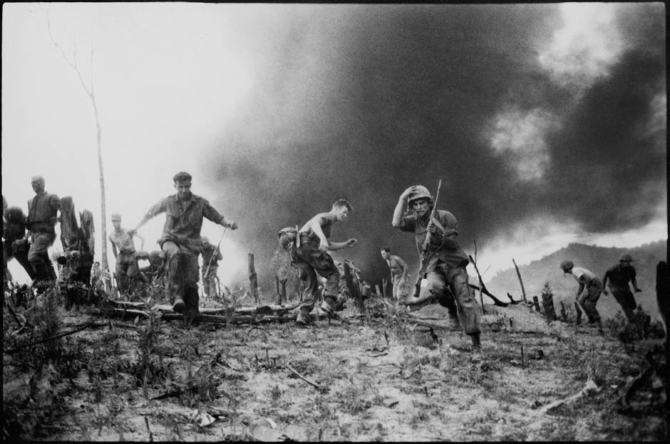 US Marines flee from the crash site of a CH-46 helicopter shot down near the demilitarized zone between North and South Vietnam