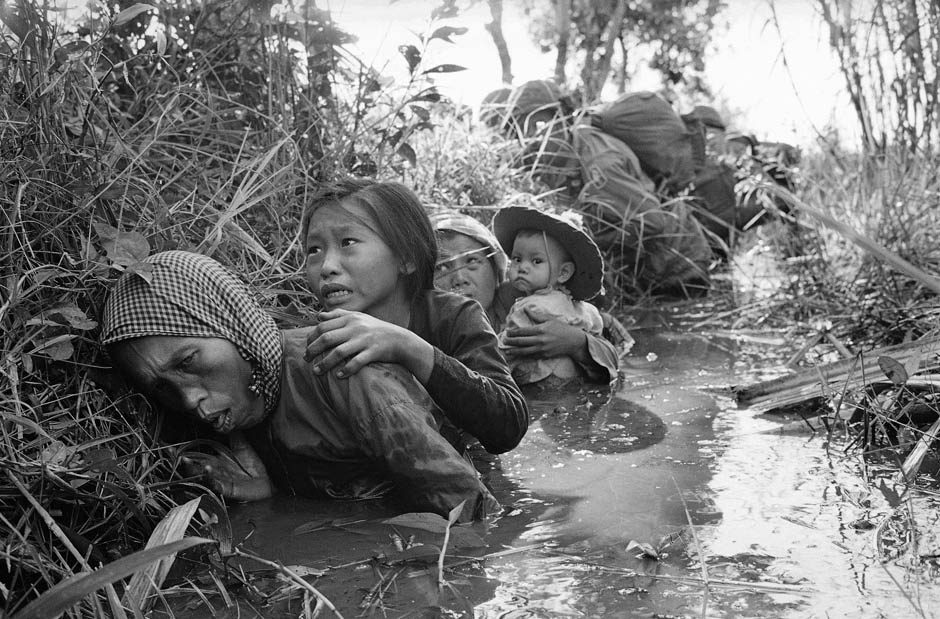 Women and children hiding in a ditch at Bao Trai, 20 miles west of Saigon