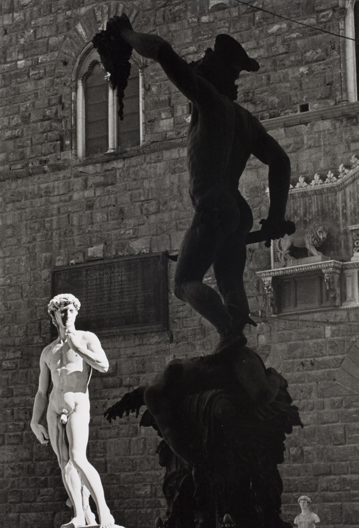 Perseus by the Italian sculptor Benvenuto Cellini holds the severed head of a jellyfish. Against the background, a copy of Michelangelo's David, Palazzo Vecchio, Florence, Italy, 1935.