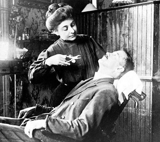 A female dentist in New York removes a tooth from a suffering patient.