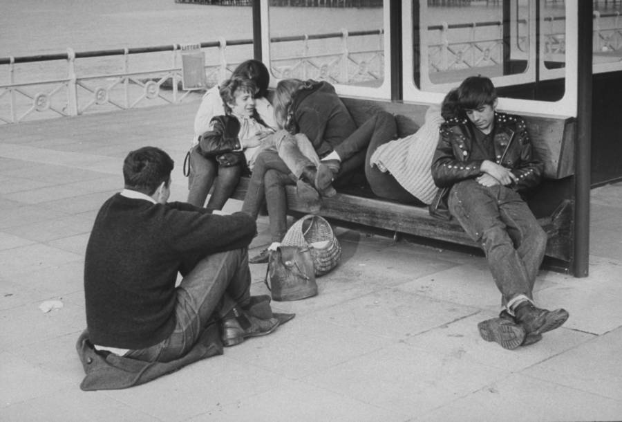 A group of rockers relaxes on a bench.