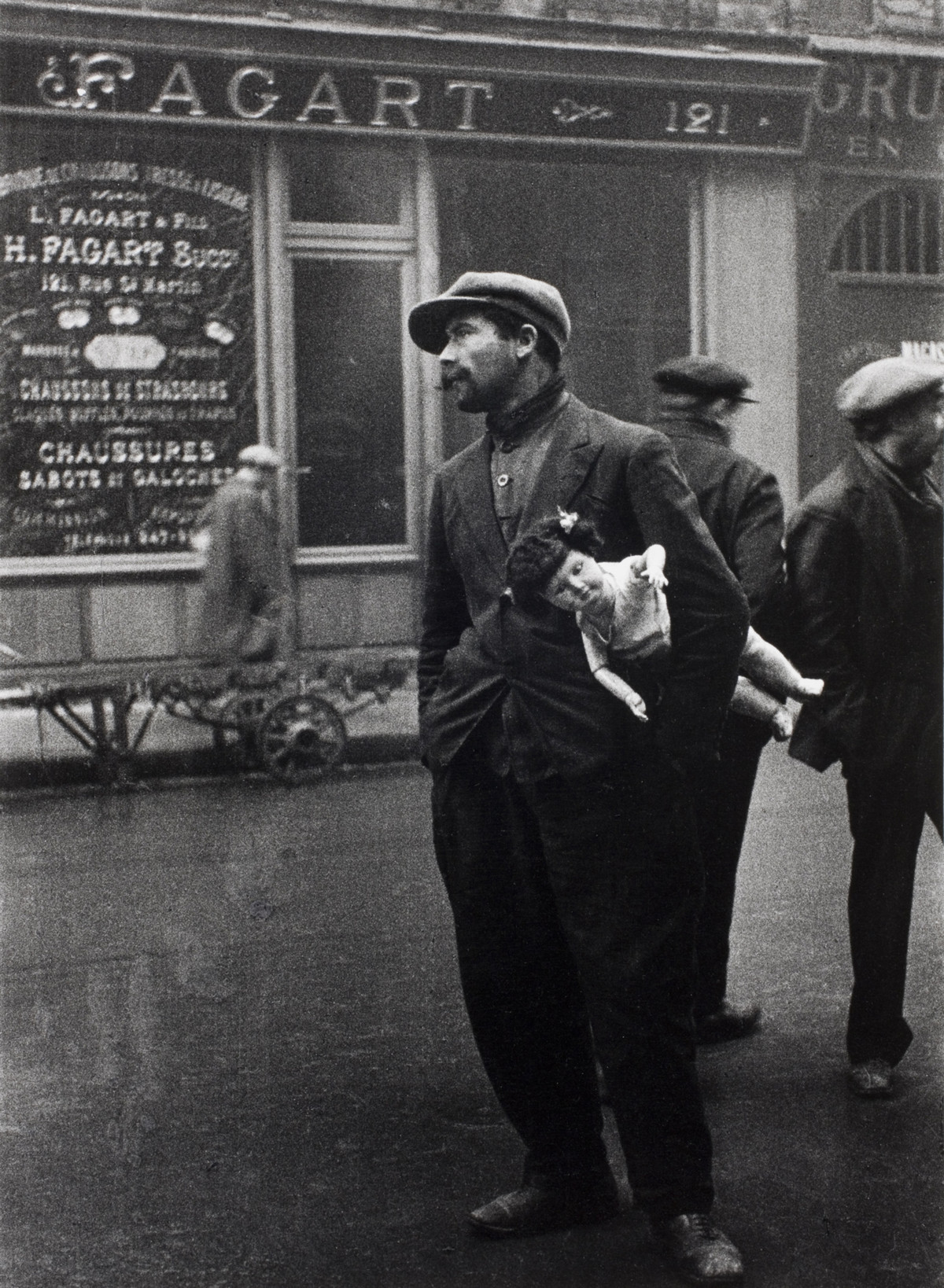 A man tries to sell a doll on the rue Saint-Denis, Paris, Ile-de-France, France, 1931.