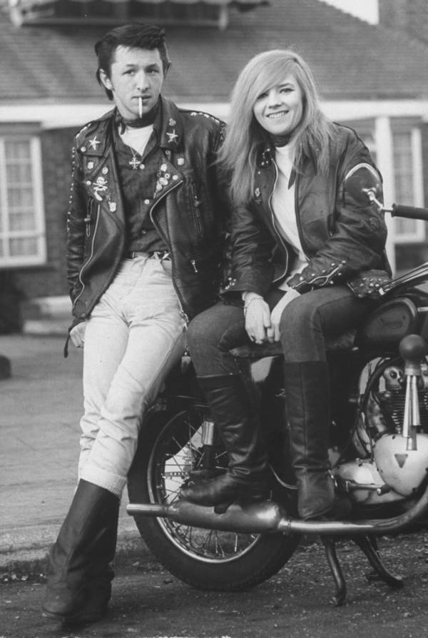 A rocker and his girlfriend pose for a Life Magazine photographer, leaning against their bike.