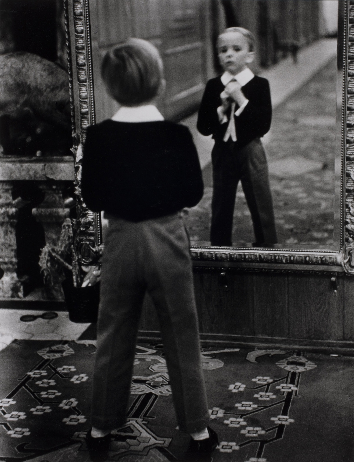 A young Englishman looks at himself in the mirror of the Grand Hotel in St. Moritz, Switzerland, 1932.