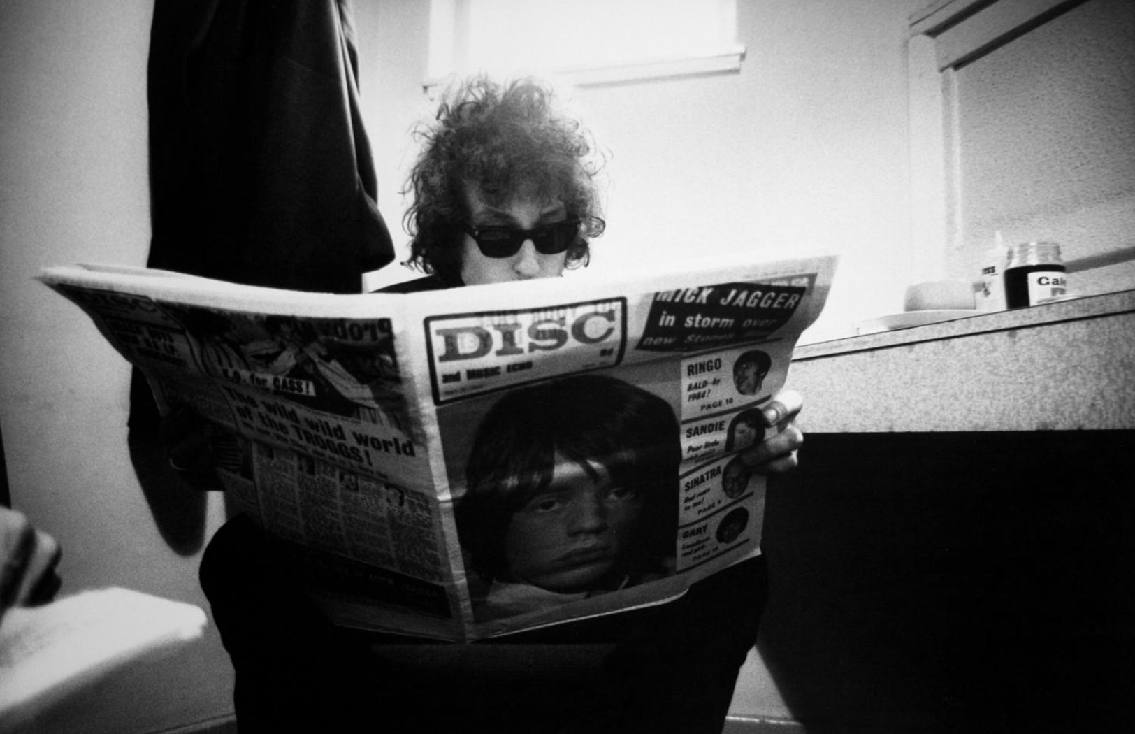 Bob Dylan, reading Disc Magazine with Mick Jagger on the cover, Odeon Theatre, Birmingham, England,
