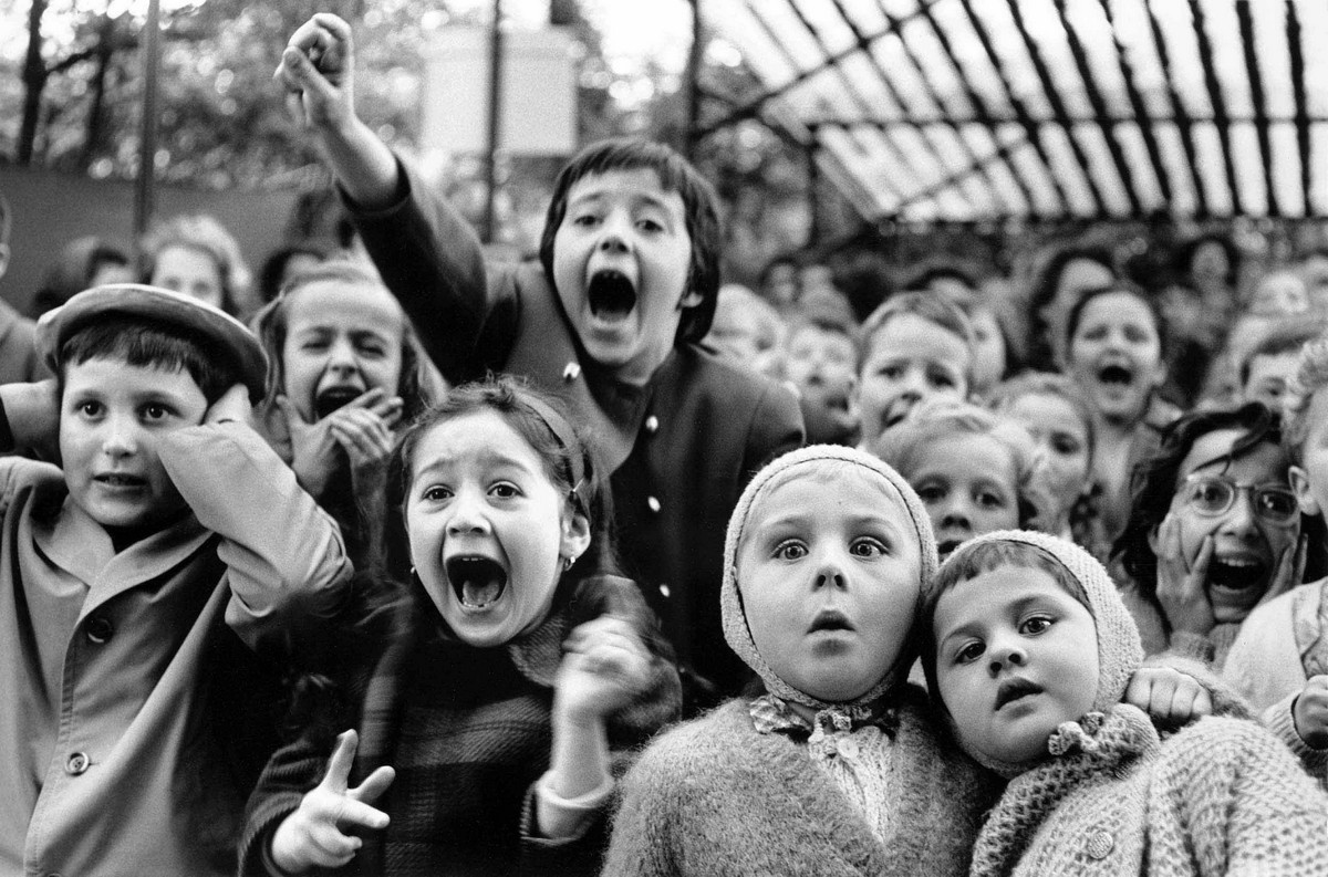 Children in the puppet theater at the moment when a bad dragon is killed. Tuileries Garden, Paris, 1963.